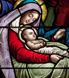 A stained class depiction of baby Jesus and the Virgin Mary