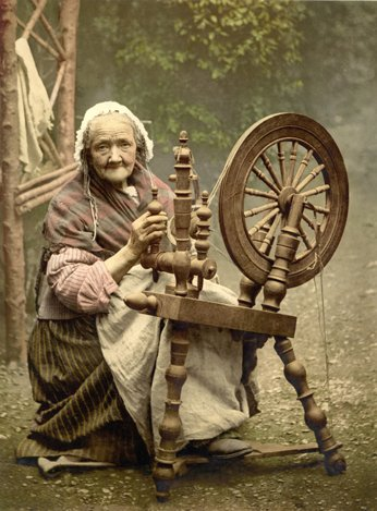 Elderly woman at spinning wheel