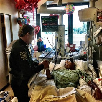 A police officer visits a shooting survivor in the hospital