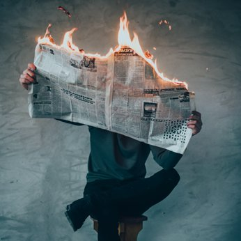 Man holding a newspaper on fire