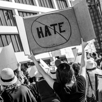 Person with sign against hate at a protest