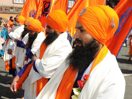 Sikhs lined up with bright orange turbans.