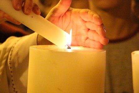A man in a religious outfit lights a candle