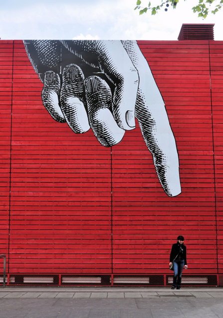 A painting on a wall with a giant hand and a finger pointing