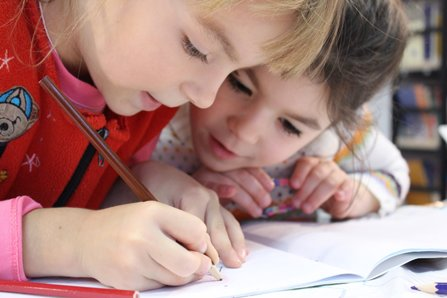 Two girls focused on drawing on a piece of paper