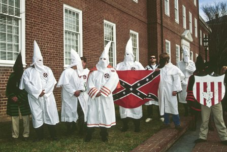 Ku Klux Klan members standing outside of a building