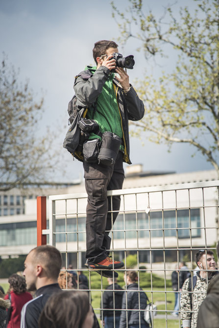 A photo journalist standing on a fence to get a shot