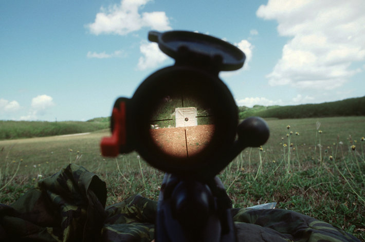 Looking through a gun at a target