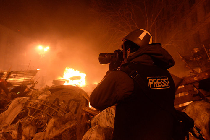 Journalist photographing a fire.