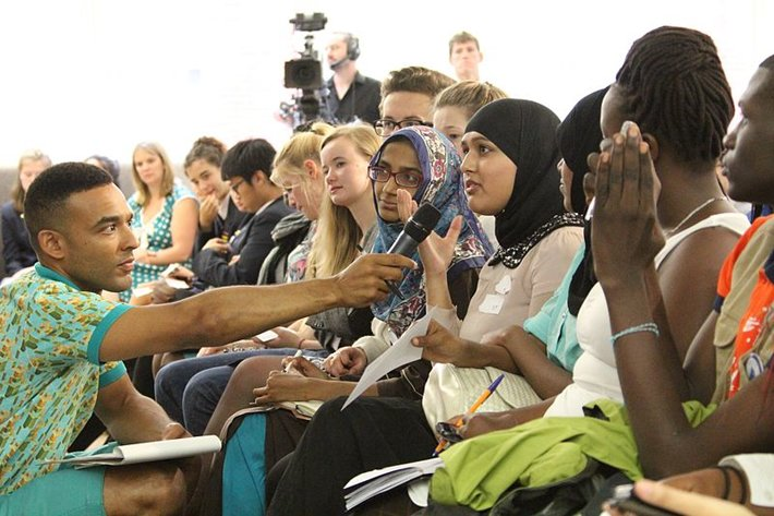 A woman in a hijab in an audience is given the microphone to speak