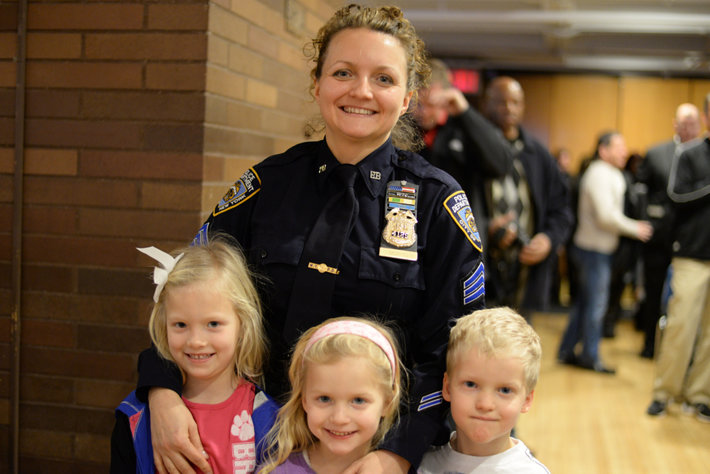 Smiling policewoman with three cute children