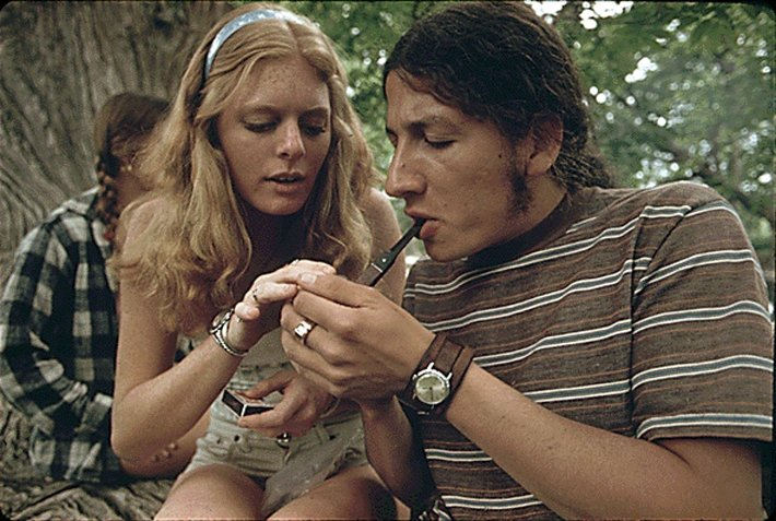 A man and a woman with a pipe smoking marijuana
