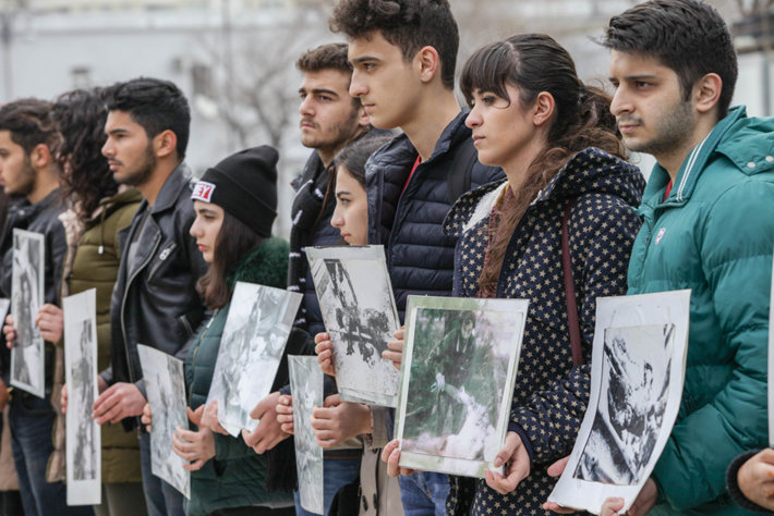 Azerbaijani tudents holding pictures of those who died in a genocide