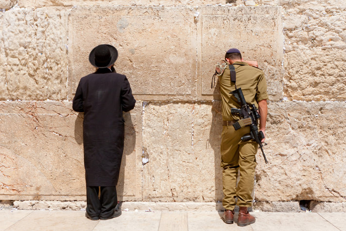 A soldier and Orthodox Jew pray at the Western Wall