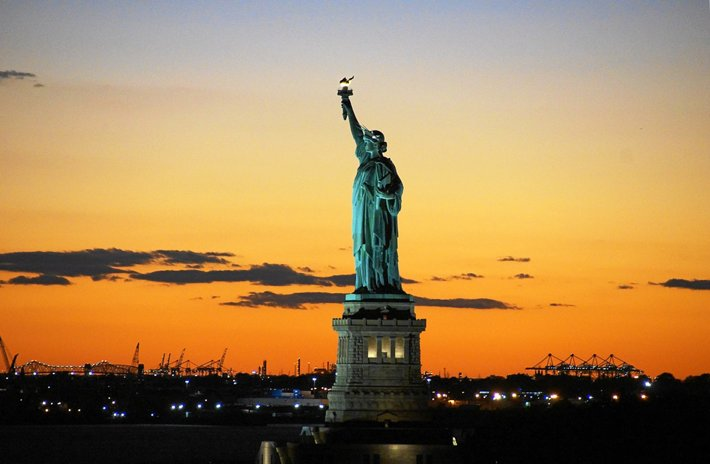 The Statue of Liberty with a sunset behind it