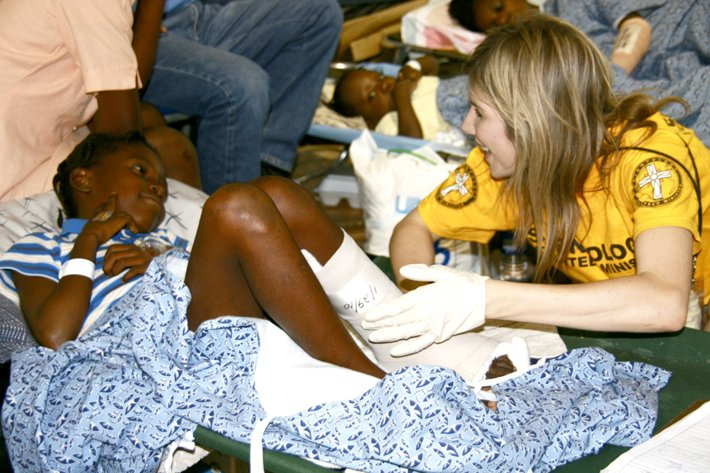 A Scientology Volunteer Minister helping a girl with a cast