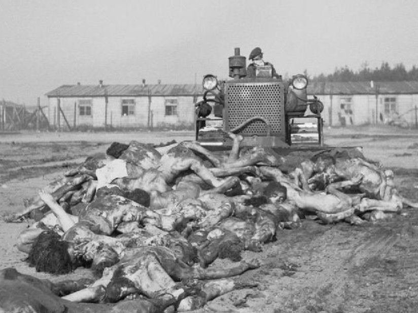 Bodies being pushed into a mass grave