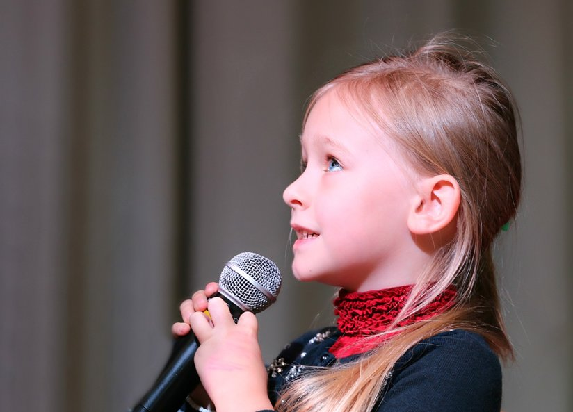 A little girl with a microphone