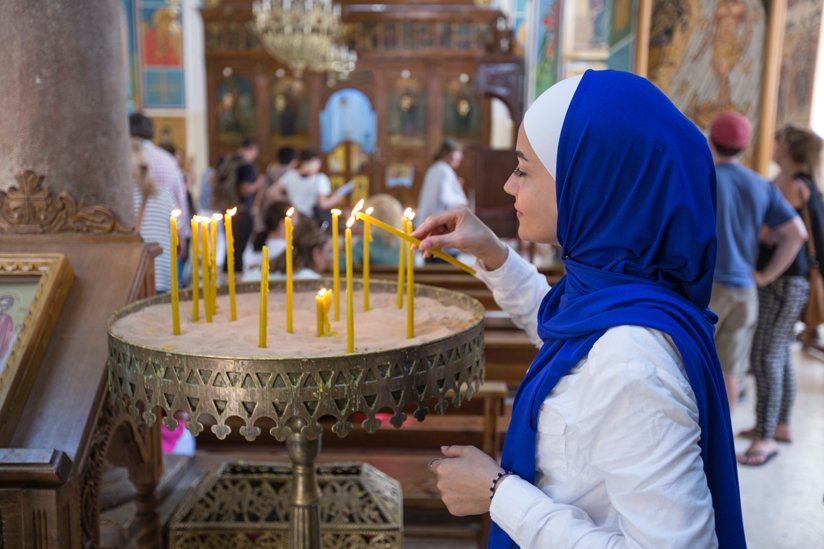 Woman in hijab lighting candles in a religious space