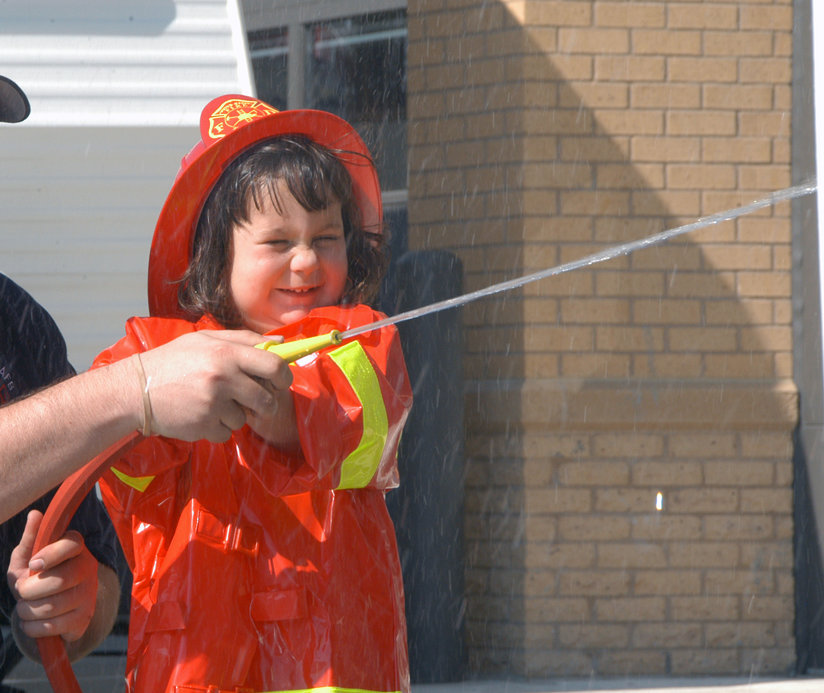 A little girl in firefighter's uniform with a hose