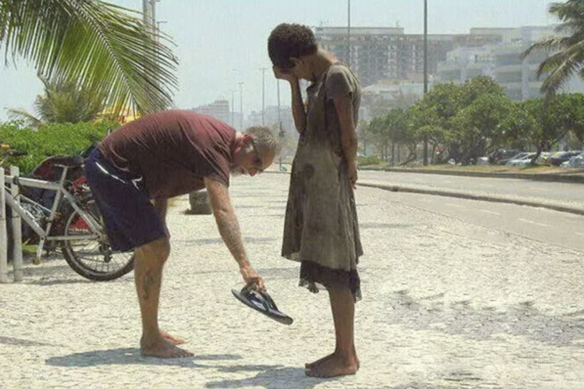 A man giving his shoes to a homeless girl in Brazil