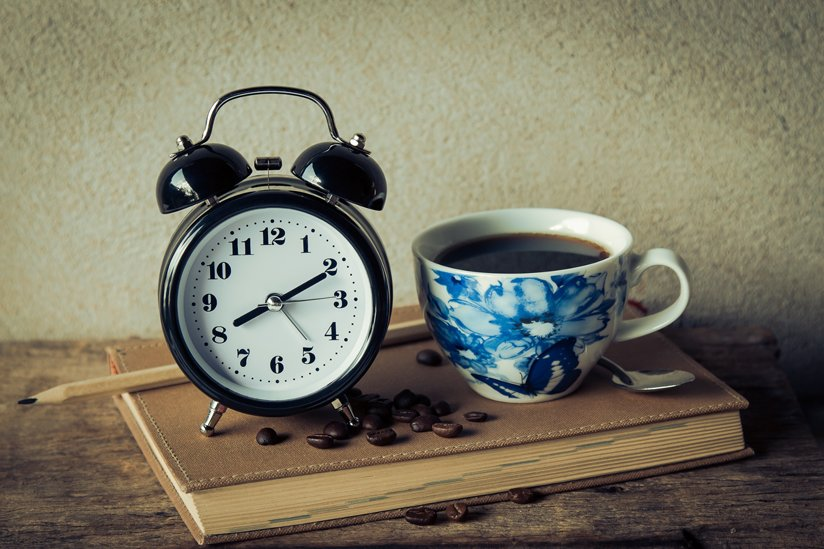 An alarm clock and a coffee cup