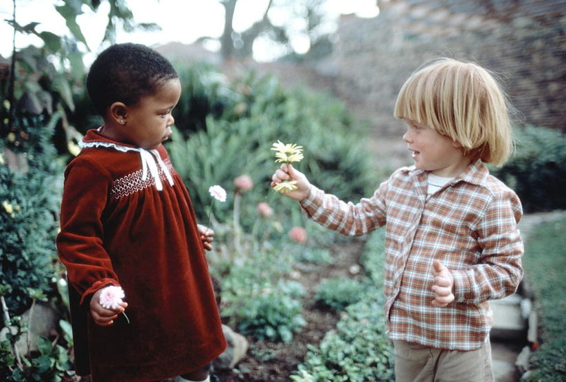 A white boy presenting a black child with a flower
