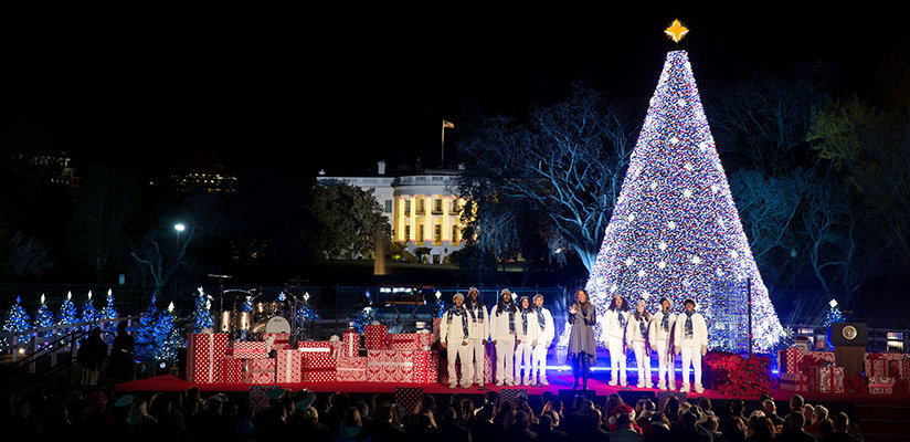 A Christmas performance in front of the White House with a large Christmas tree